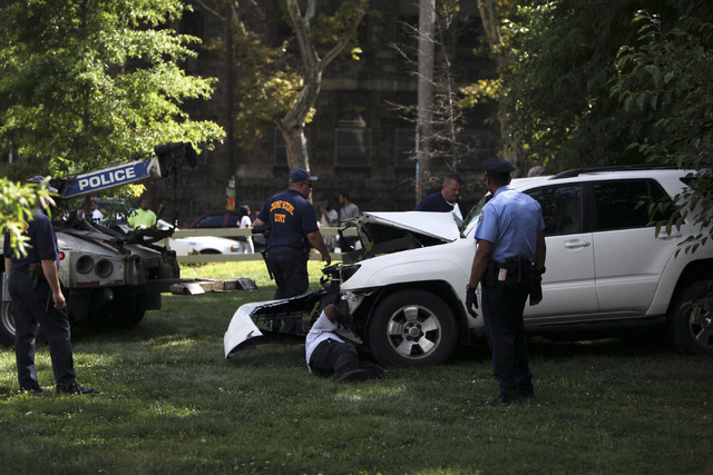Investigators examine a heavily damaged SUV before it is towed from the scene of a fatal accident in North Philadelphia, July 25, 2014. The mother of the three children killed in the crash died Th ...