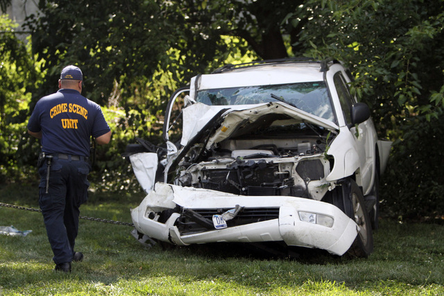 An investigator examines a heavily damaged SUV before it is towed from the scene of a fatal accident in North Philadelphia, July 25, 2014. The mother of the three children killed in the crash died ...