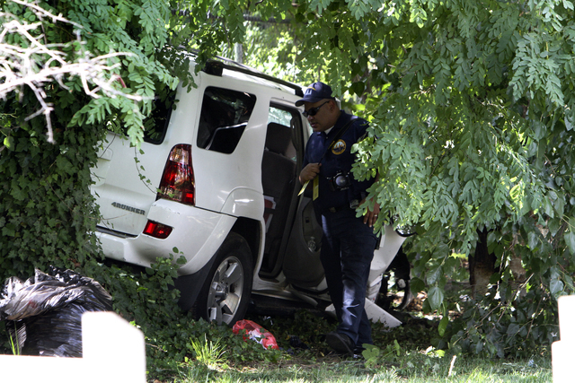 Investigators gather at the scene of a fatal accident in North Philadelphia, July 25, 2014. The mother of the three children killed in the crash died Thursday night, Aug. 7, 2014. (AP Photo/ Josep ...