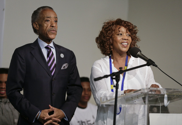 Actress Alfre Woodard, right, speaks as the Rev. Al Sharpton looks on during a rally, Saturday, Aug. 2, 2014, in New York. The rally was held to address the medical examiner's report that came Fri ...