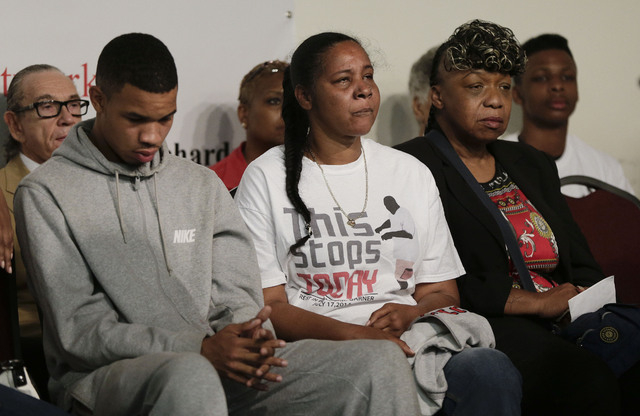 Eric Garner's son Eric Snipes, left, Eric Garner's widow Esaw Garner, center, and Eric Garner's mother Gwen Carr, listen during a rally, Saturday, Aug. 2, 2014, in New York. The rally was held to  ...