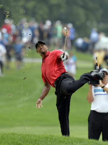 Tiger Woods makes an awkward follow through after hitting from the lip of a fairway bunker on the second hole during the final round of the Bridgestone Invitational golf tournament Sunday, Aug. 3, ...