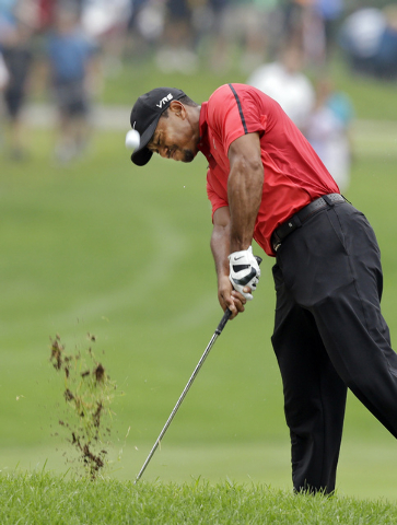 Tiger Woods hits from the lip of a fairway trap on the second hole during the final round of the Bridgestone Invitational golf tournament Sunday, Aug. 3, 2014, at Firestone Country Club in Akron,  ...