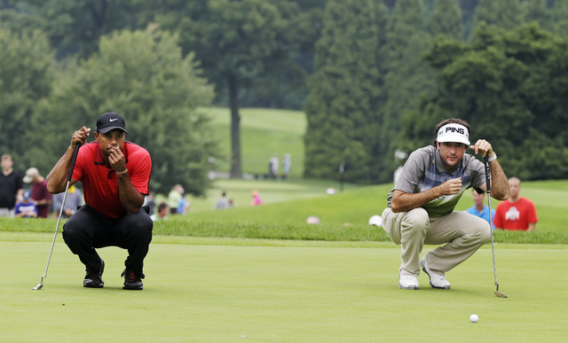 Tiger Woods, left, and Bubba Watson looks over their putts on the second hole during the final round of the Bridgestone Invitational golf tournament Sunday, Aug. 3, 2014, at Firestone Country Club ...