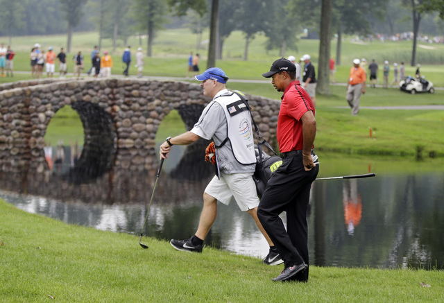 Tiger Woods and caddie Joe Lacava walk to the third green during the final round of the Bridgestone Invitational golf tournament Sunday, Aug. 3, 2014, at Firestone Country Club in Akron, Ohio. (AP ...