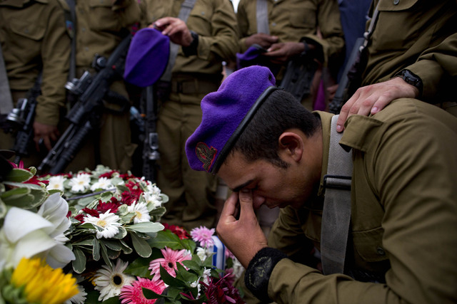 Israeli soldiers mourn over the grave of Israeli Army 2nd. Lt. Hadar Goldin during his funeral at the military cemetery in the central Israeli city of Kfar Saba on Sunday, Aug. 3, 2014. Israel ann ...