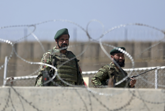 Afghanistan National Army soldiers stand guard at a gate of Camp Qargha, west of  Kabul, Afghanistan, Tuesday, Aug. 5, 2014. A man dressed in an Afghan army uniform opened fire Tuesday on foreign  ...