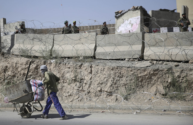 An Afghan laborer walks past a gate of Camp Qargha as Afghanistan National Army soldiers stand guard, west of  Kabul, Afghanistan, Tuesday, Aug. 5, 2014. A man dressed in an Afghan army uniform op ...
