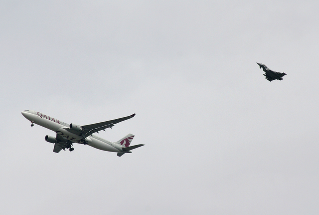 A military fighter jet escorts a passenger jet as it comes in to land at Manchester airport, Manchester, England, Tuesday, Aug. 5, 2014. Police say they have arrested a man on suspicion of making  ...