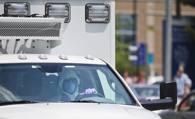 An ambulance transporting Nancy Writebol, an American missionary stricken with Ebola, arrives at Emory University Hospital, Tuesday, Aug. 5, 2014, in Atlanta. Writebol is expected to be admitted t ...