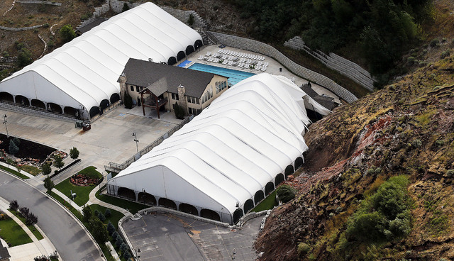 The Eagleridge Swim and Tennis Club works is damaged following a landslide in a hillside community of North Salt Lake, Utah, Tuesday, Aug. 5, 2014. One home has been destroyed and at least a dozen ...