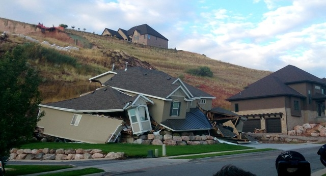 A home collapsed during a mudslide, Tuesday, Aug. 5, 2014 in North Salt Lake, Utah.  The home crumbled after rain-saturated soil from the hill above started piling up behind it at around 6 a.m. Tu ...