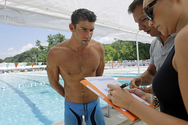 In this July 31, 2014 photo, Michael Phelps, left, goes over details of a prototype swimsuit with designers before a training session at Meadowbrook Aquatic and Fitness Center in Baltimore. After  ...