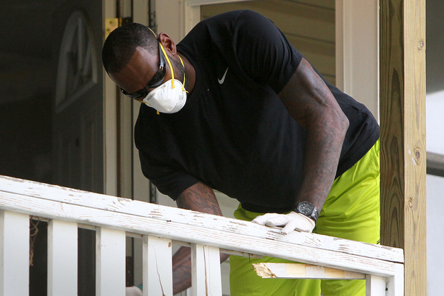 LeBron James knocks the spindles out of a railing at a rehab site on Monday, Aug. 4, 2014, in Akron, Ohio.  James took the controls of a backhoe to help fix up a crumbling house for the family of  ...