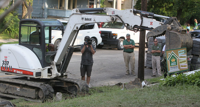 LeBron James operates an excavator as a camera operator and Darren Rowland and Brian Rice of Rice Nursery and Landscaping, look on at a rehab site on Monday, Aug. 4, 2014, in Akron, Ohio. His sons ...