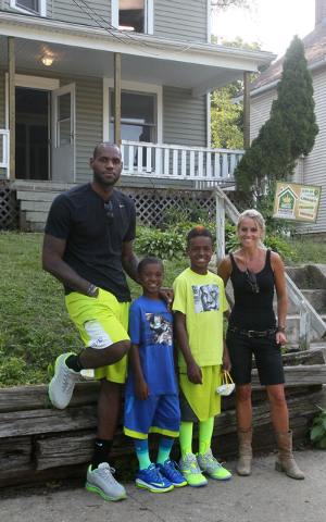 TV's Rehab Addict host Nicole Curtis, right, poses with LeBron James and his sons, LeBron Jr., and Bryce at a rehab site on Monday, Aug. 4, 2014, in Akron, Ohio.  James took the controls of a back ...