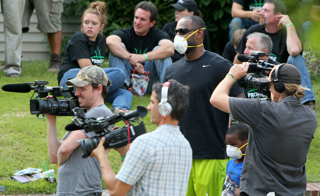 LeBron James and his son, Bryce, look on from a click of camera operators at a rehab site on Monday, Aug. 4, 2014, in Akron, Ohio.  James took the controls of a backhoe to help fix up a crumbling  ...