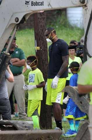 LeBron James and his sons, LeBron Jr., left,  and Bryce, head to the heavy equipment at a rehab site on Monday, Aug. 4, 2014, in Akron, Ohio.  James took the controls of a backhoe to help fix up a ...