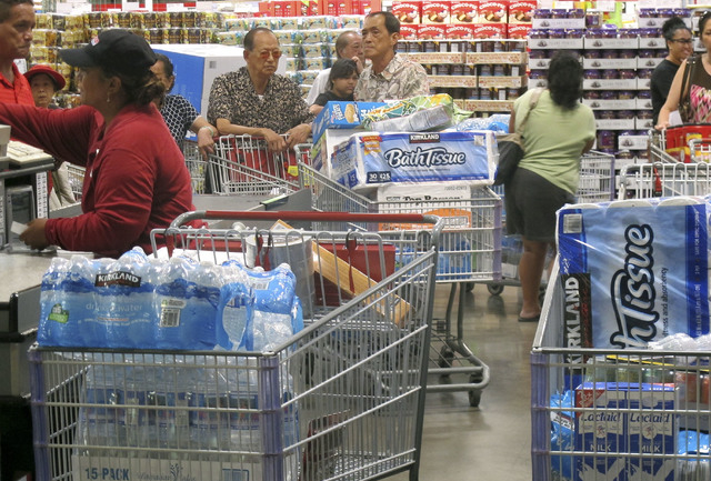 Shoppers stock up on cases of bottled water and other supplies in preparation for a hurricane and tropical storm heading toward Hawaii at the Iwilei Costco in Honolulu on Tuesday, Aug. 5, 2014. Tw ...