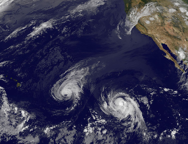 This image provided by NOAA taken Wednesday Aug. 6, 2014 shows Hurricane Iselle, center, and tropical storm Julio, right. Though it's not clear how damaging the storms could be, many in Hawaii are ...