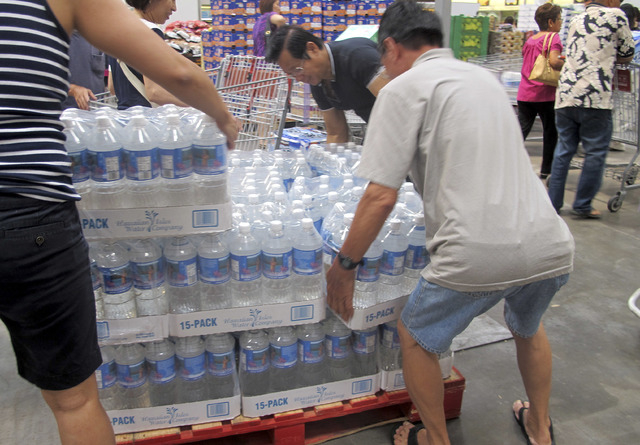 Shoppers lift cases of bottled water in preparation for a hurricane and tropical storm heading toward Hawaii at the Iwilei Costco in Honolulu on Tuesday, Aug. 5, 2014. Two big storms so close toge ...