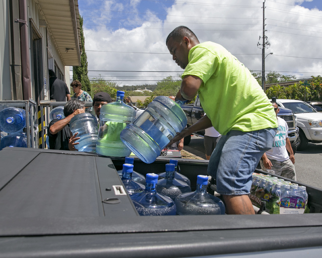 Workers at the Menehune Water Company load five gallon bottles of water into a customer's truck, Thursday, Aug. 7, 2014, in Aiea, Hawaii.  Hawaii is bracing for two back to back hurricanes, Iselle ...