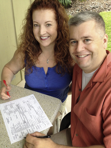 This Wednesday, Aug. 6, 2014 photo released by Emily Kreifels shows Tracy Black, left, and Chris Kreifels as they sign their marriage license application in Kailua-Kona, Hawaii. Washington state c ...