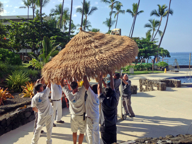 Staff members of the Royal Kona Resort in Kailua, Hawaii take down umbrellas as the resort prepares for Hurricane Iselle on Thursday, Aug. 7, 2014. Hurricane Iselle is expected to arrive on the Bi ...