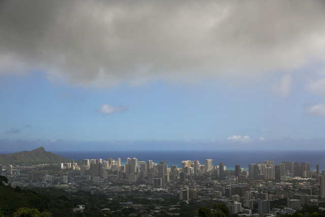 Clouds hang over Honolulu, seen from the top of Tanalus Drive on Thursday, Aug. 7, 2014. With Iselle, Hawaii is expected to take its first direct hurricane hit in 22 years. Tracking close behind i ...