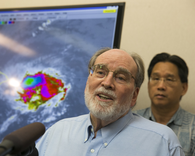 Hawaii Gov. Neil Abercrombie, center, speaks at the National Weather Service office on the campus of the University of Hawaii, Thursday, Aug. 7, 2014, in Honolulu.  Hawaii is bracing for both Hurr ...