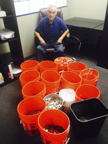 This image provided by Andres Carrasco shows him in his office in Los Angeles, July 31, 2014 with buckets of change he won as a partial settlement in a 2012 lawsuit against Adrianas Insurance Serv ...