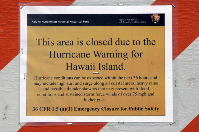 A hurricane warning sign is shown posted on the beach in Kailua, Hawaii, Thursday, Aug. 7, 2014. A weakened Tropical Storm Iselle made landfall Friday on Hawaii. Tracking close behind it is Hurric ...