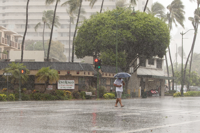 A man uses an umbrella against the rain as he walks across Kapiolani Blvd in Waikiki in Honolulu on Friday, Aug. 8, 2014. Iselle came ashore early Friday as a weakened tropical storm, while Hurric ...
