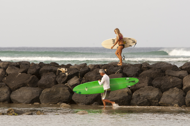 Two surfers head for the waves in Honolulu on Friday, Aug, 8, 2014. High surf is expected in some spots on Oahu due to Tropical Storm Iselle. (AP Photo/Marco Garcia)