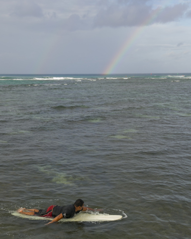 With a rainbow in the background, a surfer paddles to shore in Honolulu on Friday, Aug, 8, 2014. Iselle came ashore early Friday as a weakened tropical storm, while Hurricane Julio, close behind i ...