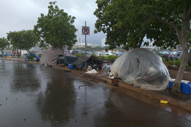 Homeless people take shelter in their camp near Kakaako Waterfront Park in Honolulu on Friday, Aug, 8, 2014. Iselle came ashore early Friday as a weakened tropical storm, while Hurricane Julio, cl ...