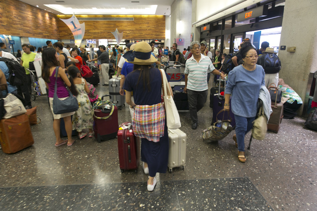 Crowds line up inside the departures terminal at the Honolulu International Airport in Honolulu on Thursday, Aug. 7, 2014. A weakened Tropical Storm Iselle made landfall Friday on Hawaii. Tracking ...