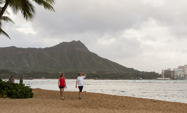 Visitors Sharon Zappa, left, of Florida, and Vicki Stearns, of Chicago, walk along the beach in Waikiki in Honolulu on Friday, Aug, 8, 2014. Iselle came ashore early Friday as a weakened tropical  ...