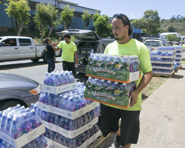 A worker at the Menehune Water Company carries bottle of water to waiting customers, Thursday, Aug. 7, 2014, in Aiea, Hawaii. A weakened Tropical Storm Iselle made landfall Friday on Hawaii. Track ...