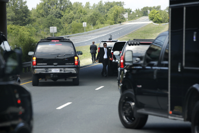 Secret Service agents walk from a vehicle as the motorcade carrying President Barack Obama stops on the highway en route to Fort Belvoir, Va., Thursday, Aug. 7, 2014, due to a slight mechanical is ...