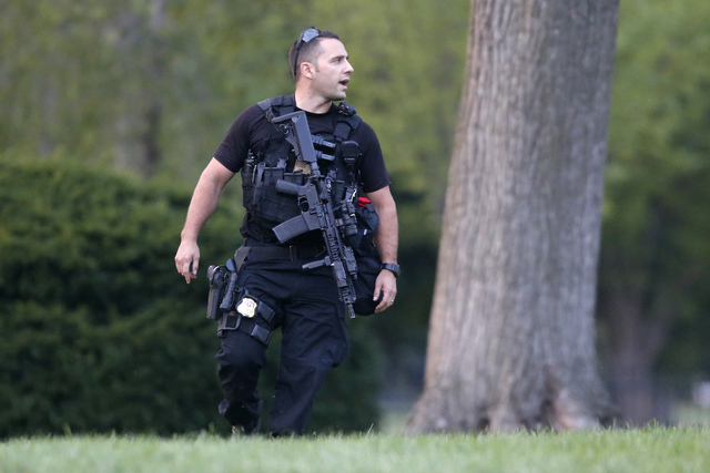 A member of the U.S. Secret Service Emergency Response Team stands watch on the North Lawn at the White House in Washington, Thursday, Aug. 7, 2014.  A toddler passing through slats in the gate ca ...