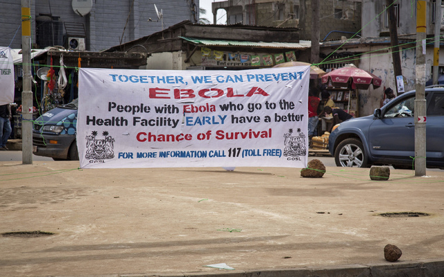 A banner encouraging people suffering from Ebola to go immediately to a health center for treatment is seen on a sidewalk in the city of  Freetown, Sierra Leone, Thursday, Aug. 7, 2014. While the  ...