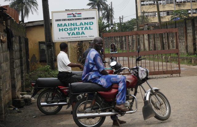Motorcycle taxi men wait outside the gate of Mainland hospital were suspected Ebola virus victims are quarantined in Lagos, Nigeria, Thursday, Aug. 7, 2014.  Authorities in West African are battli ...