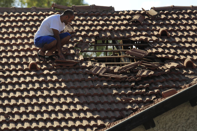 An Israeli man examines the damage to the roof of his house after a rocket fired from Gaza hit in a residential neighborhood of the southern city of Sderot, Israel, Friday, August 8, 2014. (AP Pho ...