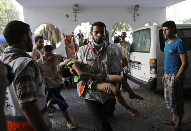 A Palestinian medic carries a wounded girl into the Shifa hospital in Gaza City, Friday, Aug. 8, 2014, as Israel and Gaza militants resumed cross-border attacks after a three-day truce expired and ...