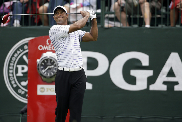 Tiger Woods watches his tee shot  on the first hole during the second round of the PGA Championship golf tournament at Valhalla Golf Club on Friday, Aug. 8, 2014, in Louisville, Ky. (AP Photo/Jeff ...