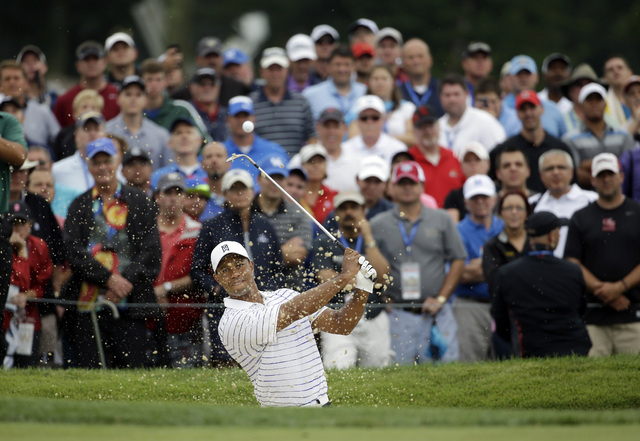 Tiger Woods hits out of the bunker on the first hole during the second round of the PGA Championship golf tournament at Valhalla Golf Club on Friday, Aug. 8, 2014, in Louisville, Ky. (AP Photo/Jef ...