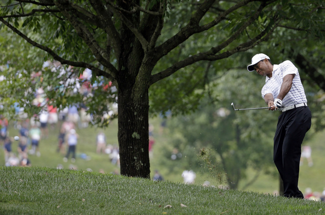 Tiger Woods hits from rough on the first hole during the second round of the PGA Championship golf tournament at Valhalla Golf Club on Friday, Aug. 8, 2014, in Louisville, Ky. (AP Photo/Jeff Roberson)