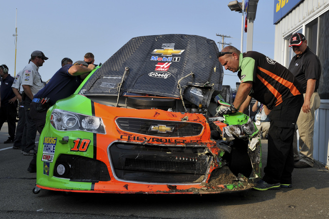 Crew members look over Danica Patrick's car after she crashed during a practice session for Sunday's NASCAR Sprint Cup series auto race at Watkins Glen International, Friday, Aug. 8, 2014, in Watk ...