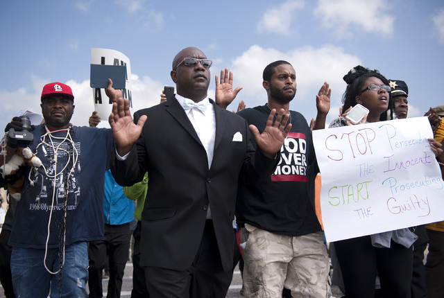 Protestors march along Florissant Road in downtown Ferguson, Mo., Monday, Aug. 11, 2014. The group marched along the closed street, rallying in front of the town's police headquarters to protest t ...